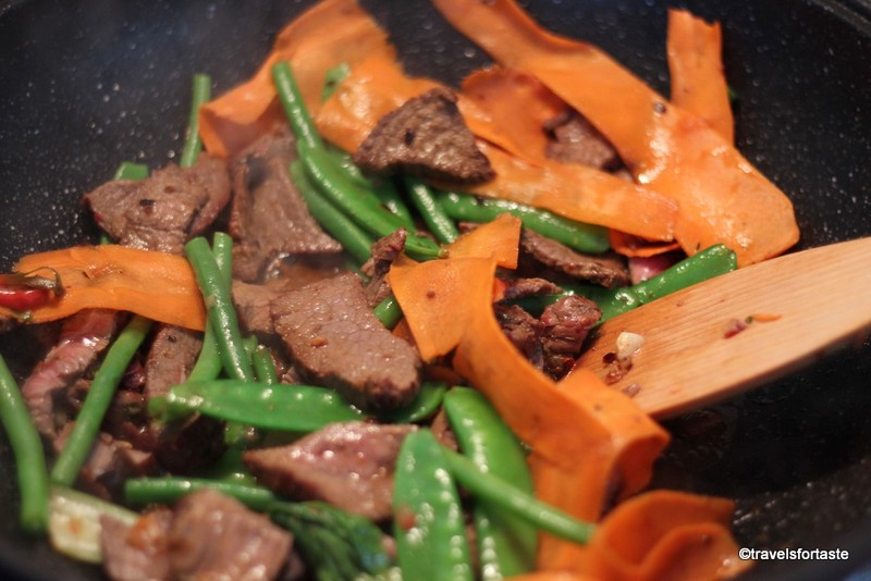 Mixing the vegetables and the stir fried beef